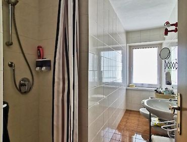 bathroom with shower and window